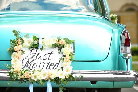 Hermoso coche de boda con placa RECIÉN CASADO al aire libre