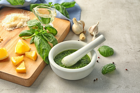 Delicious sauce in mortar with pestle and ingredients on grey background