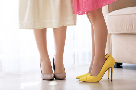 Mother and daughter in shoes at home