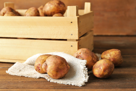 Wooden box with potatoes on wooden background