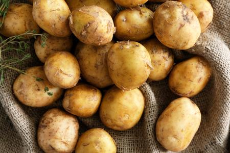 Raw organic potato on sackcloth Imagens