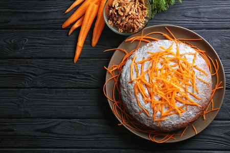 Delicious carrot cake with powdered sugar on wooden background