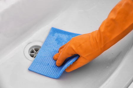 Female hand with sponge cloth cleaning a sink in the bathroom