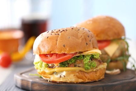 Two turkey burgers on wooden board, close up