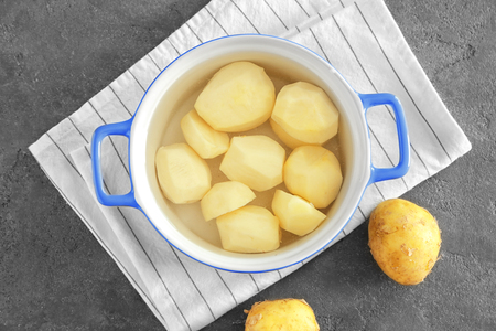 Cooking pot with raw organic potatoes on table