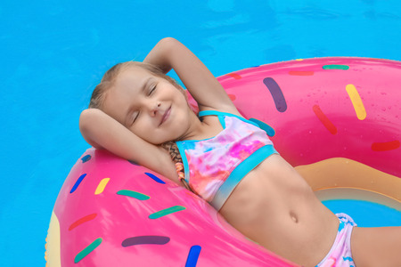 Cute little girl on inflatable donut in swimming pool Banco de Imagens - 110842337