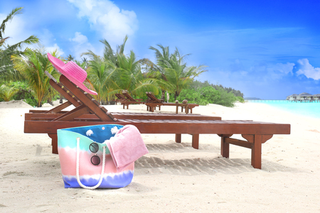 Wooden sun loungers with beach accessories at sea resort