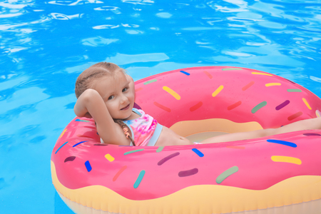 Cute little girl on inflatable donut in swimming pool