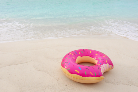 Colorful inflatable donut on sand at sea coast Фото со стока