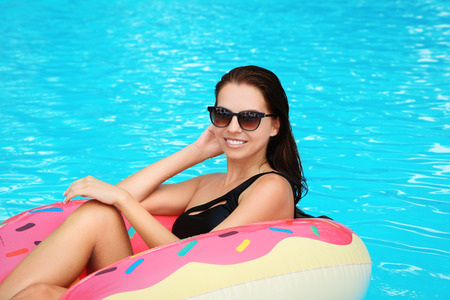 Beautiful young woman on inflatable donut in swimming pool Standard-Bild