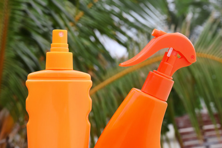 Bottles of sunscreen cream and blurred tropical palms on background, closeup. Summer vacation concept 版權商用圖片