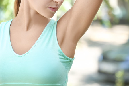 Young woman with wet spot on clothes under armpit outdoors. Concept of using deodorant Stockfoto