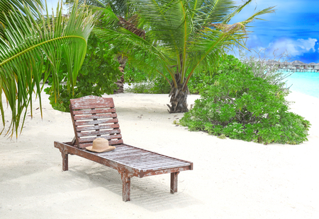 Sun lounger with hat on beach in summer day