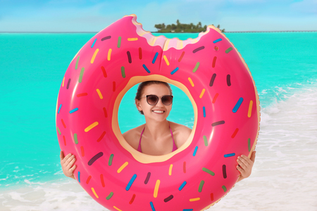 Beautiful young woman with colorful inflatable donut at sea coast