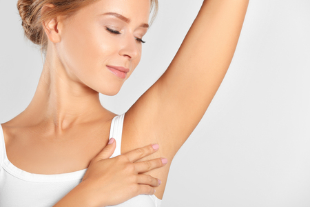 Beautiful young woman on light background. Concept of using deodorant Stockfoto - 110846901