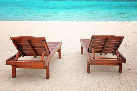 Wooden sun loungers on sea beach in summer day 写真素材