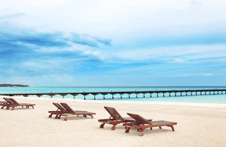 Wooden sun loungers on beach at sea resort