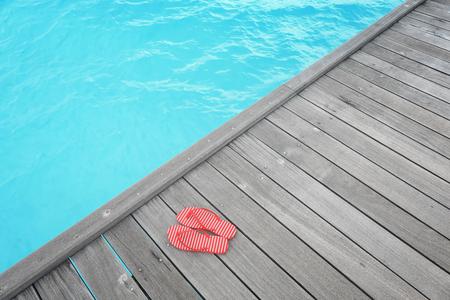 Flip-flops on wooden pontoon at sea resort. Summer vacation concept