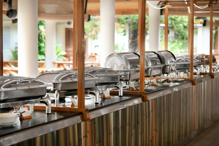 Chafing dishes with food in modern cafe
