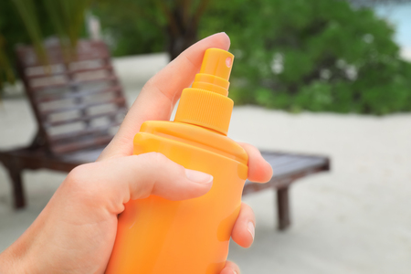 Female hand with bottle of sunscreen cream and blurred tropical beach on background, closeup. Summer vacation concept