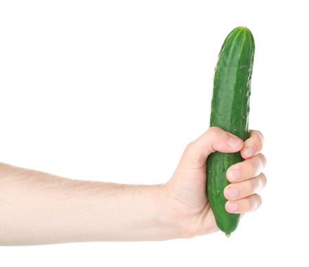 Male hand holding cucumber on white background. Sexual potency concept Фото со стока