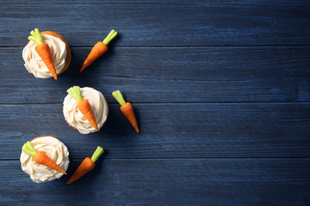 Delicious carrot cupcakes on wooden background