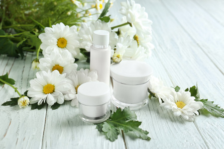 Composition with skin care products and chamomile flowers on wooden table