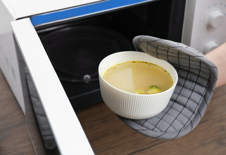 Woman taking bowl with delicious soup out of microwave in kitchen