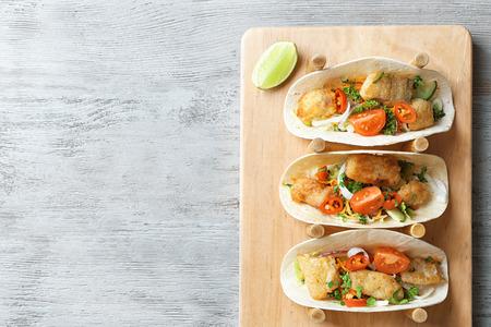 Stand con deliciosos tacos de pescado sobre fondo de madera