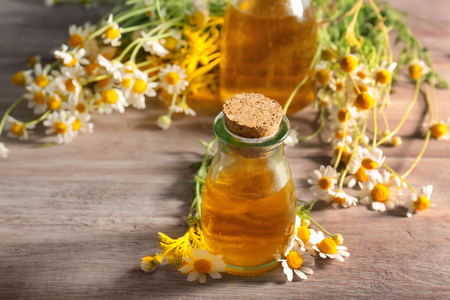 Bottle of essential oil and chamomile flowers on wooden table Stock fotó