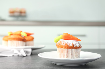 Plate with delicious carrot muffin on table