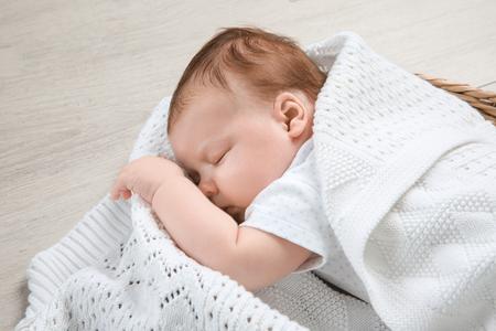 Cute newborn baby sleeping in basket at home