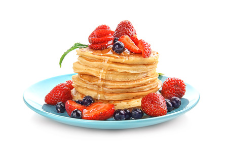 Plate with tasty pancakes and berries on white background 免版税图像