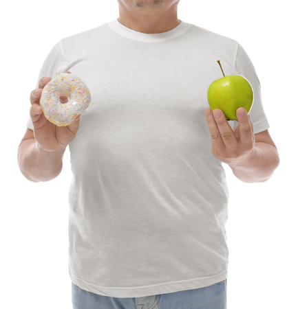 Overweight man with apple and donut on white background. Diet concept Stock Photo
