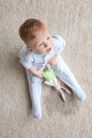 Cute baby boy sitting on carpet and playing with bunny near wet spot
