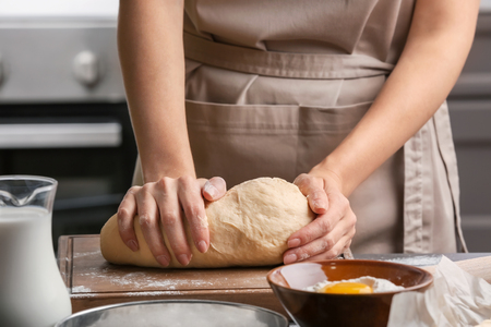 Female chef kneading dough on wooden board at kitchen