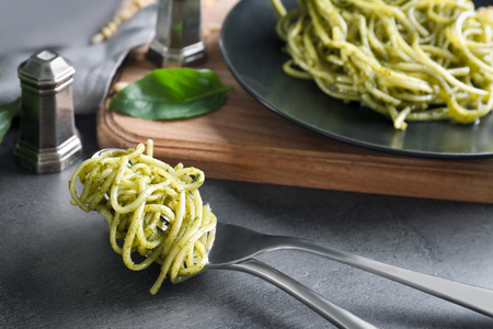 Delicious pasta with pesto sauce on table
