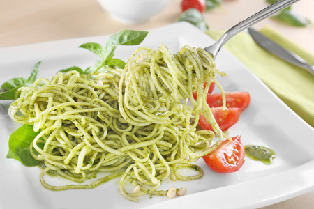 Delicious pasta on fork with pesto sauce over plate, closeup