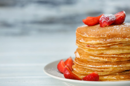 Plate with delicious pancakes on blurred background