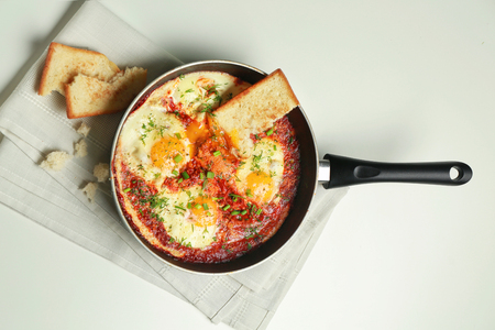 Frying pan with eggs in purgatory on napkin Imagens - 112075417