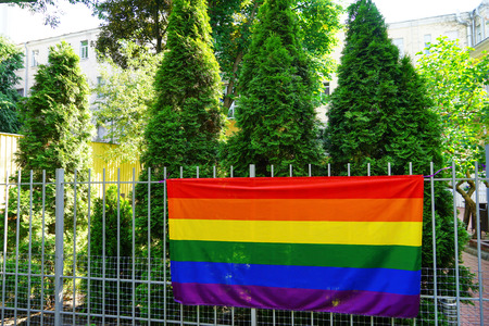 Gay flag on fence outdoors Imagens
