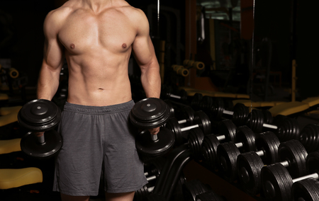 Sporty young man doing exercise with dumbbells in gym Imagens