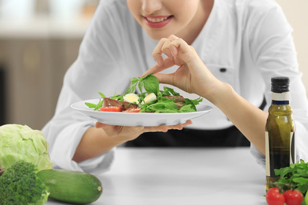 Young female chef with tasty dish in kitchen