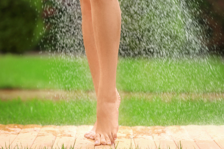 Beautiful young woman taking shower outdoors Reklamní fotografie