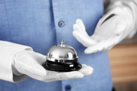 Man holding bell on blurred background, closeup