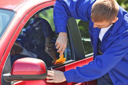 Worker applying tinting foil onto car window