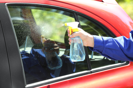 Worker cleaning car window prior to applying tinting foil