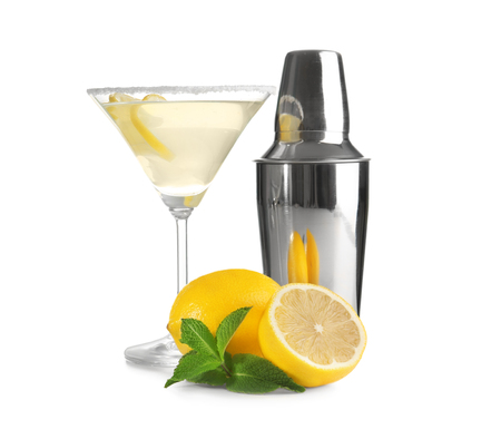 Glass of lemon drop martini, shaker and fruit on white background