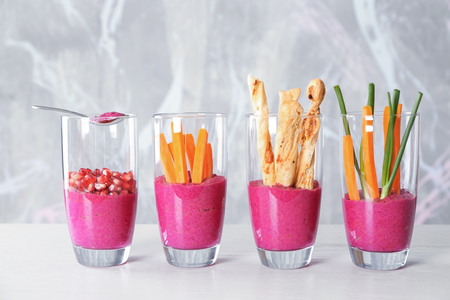 Glasses with fresh beet hummus on table