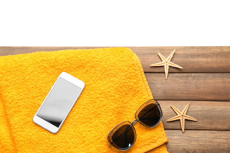 Composition with phone and sunglasses on wooden board. Vacation concept Foto de archivo